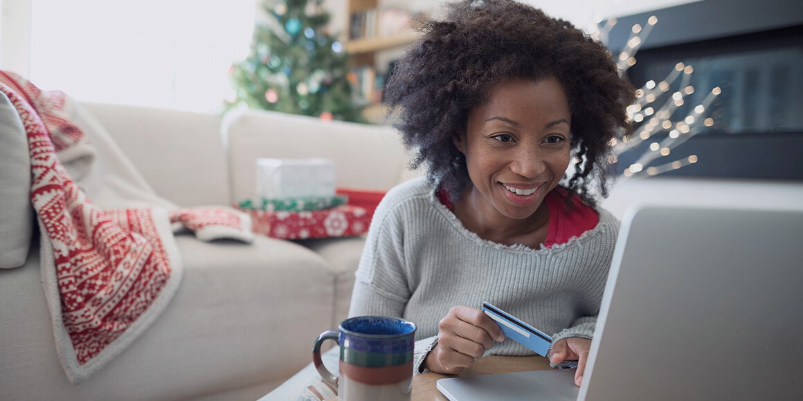 A woman sitting in her Christmas decorated living room making a purchase on her laptop.