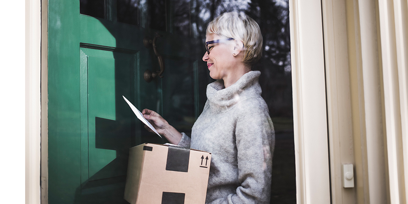A woman looking at mail and a package she's received at home and smiling.