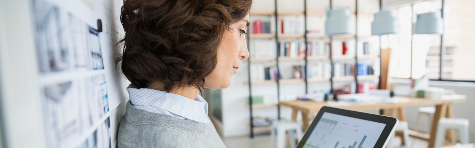 Female professional in an office, leaning against a wall and looking at a tablet.