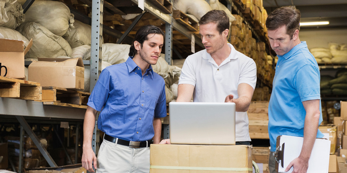Three warehouse workers in conversation, looking at a laptop.