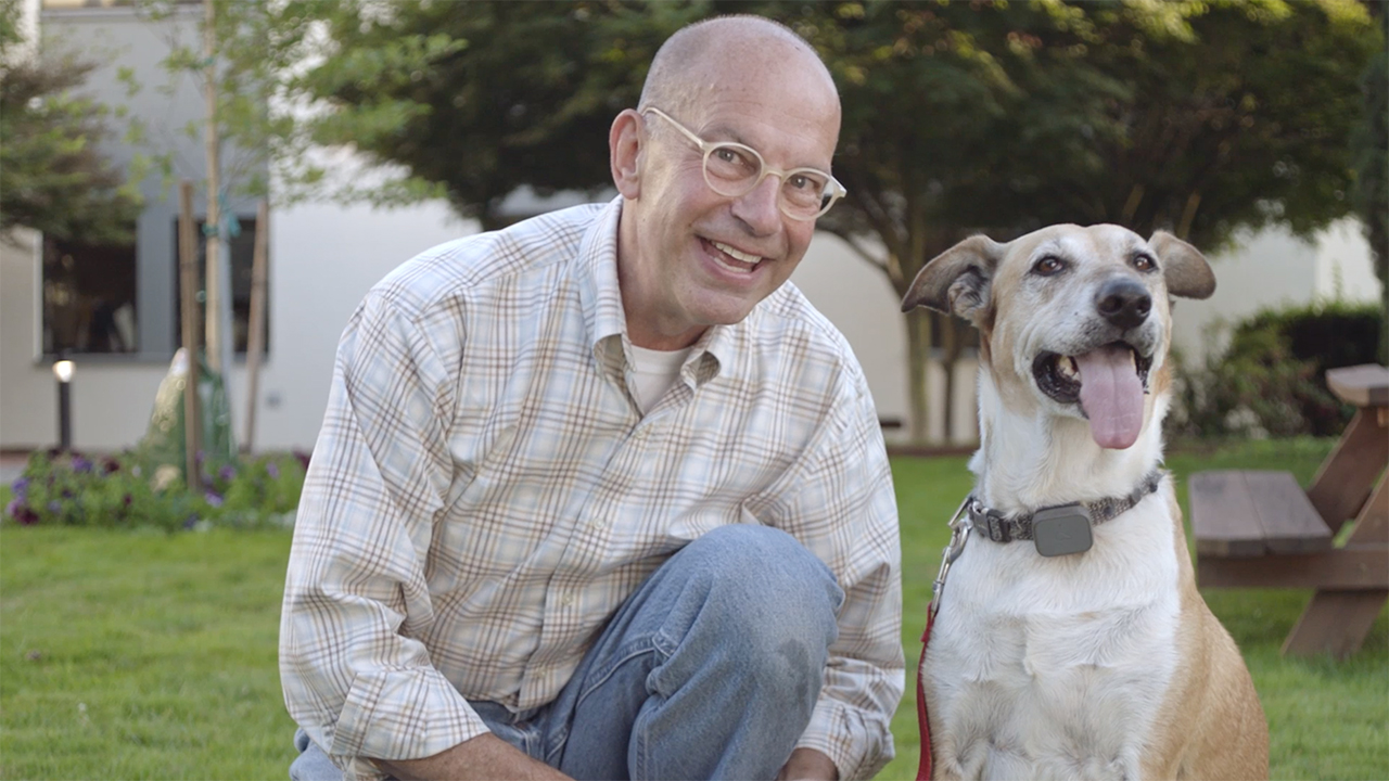 A man smiling and sitting next to a dog.
