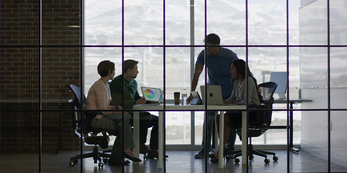 Four people in a glass-enclosed office working together and off computers.