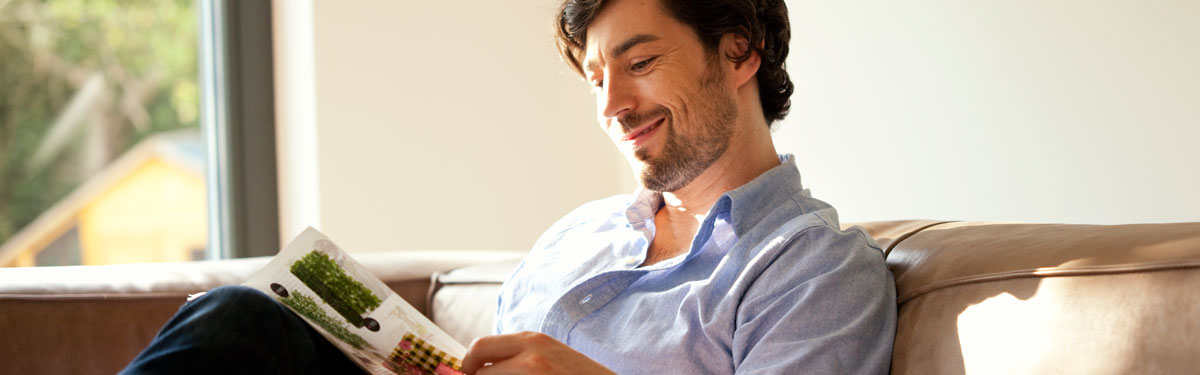 A man relaxing on a leather couch reading magazine.