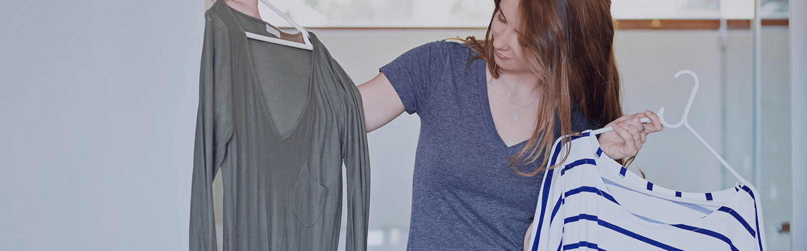 A female professional comparing two shirts.