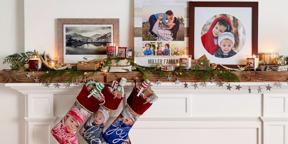 A fireplace decorated for the holiday season with family photos and stockings.
