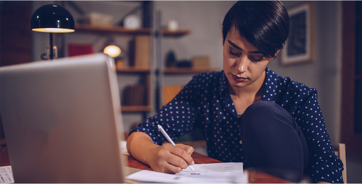 A woman sitting by her laptop doing paperwork.