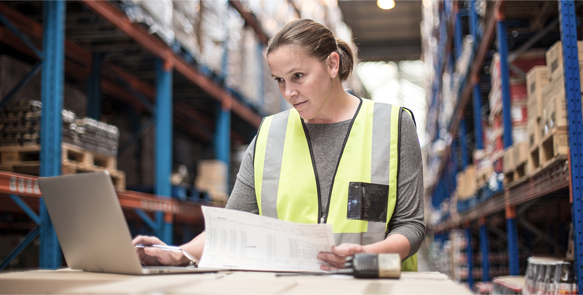 A warehouse worker reading logistics and comparing data against her laptop computer.