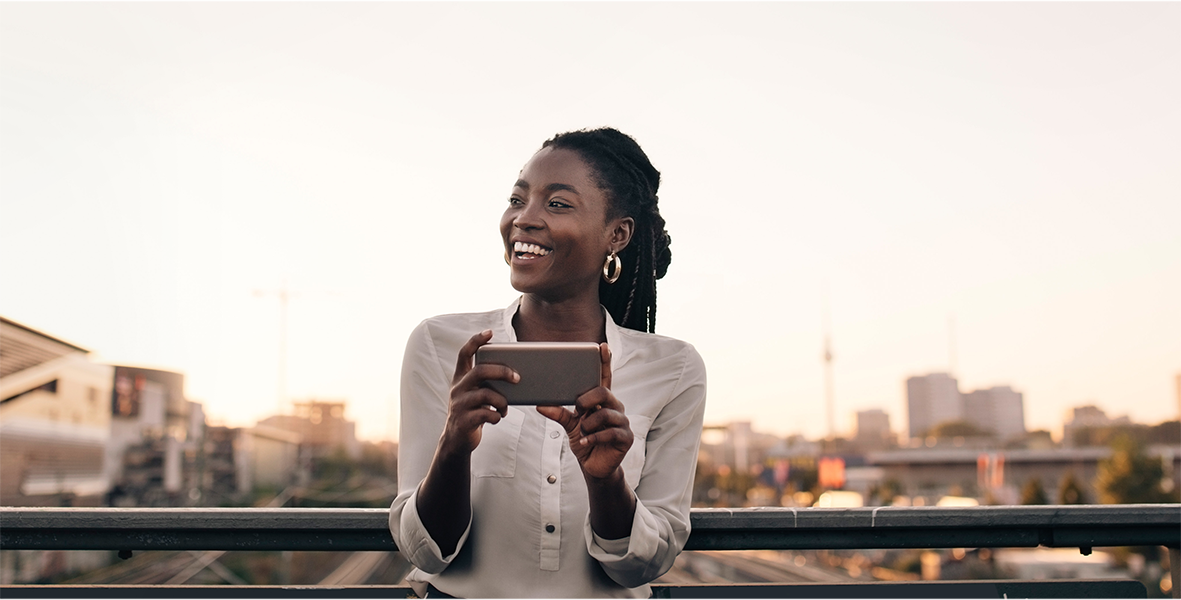 A woman laughing as she's engaged with her cell phone.