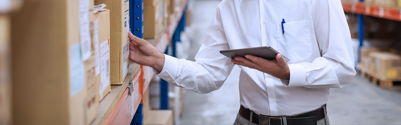A professional in a white shirt holding a tablet and checking up a package in a warehouse.