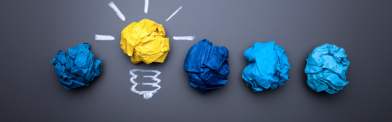 Five pieces of crumpled up pieces of paper with one depicting a light bulb.