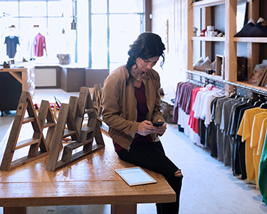 A woman sitting on a wooden table in a clothes shop.
