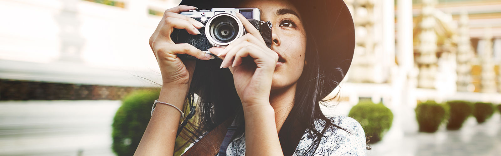 A woman wearing a hat taking a picture with her camera.