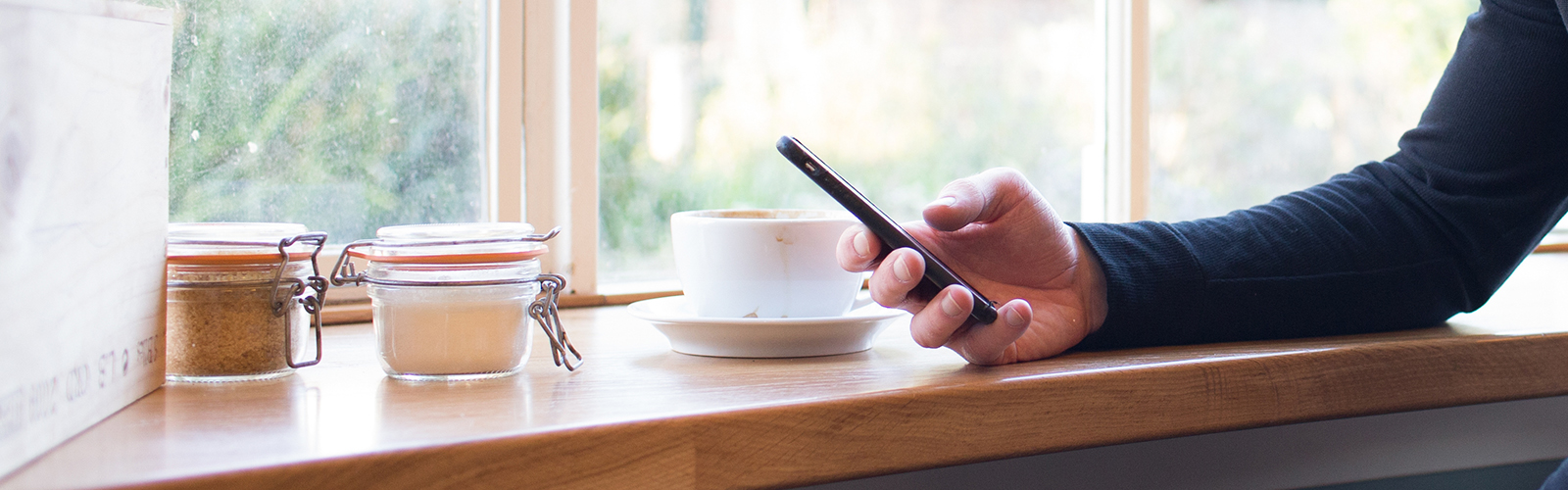 A person on their cell phone while drinking a cup of coffee.