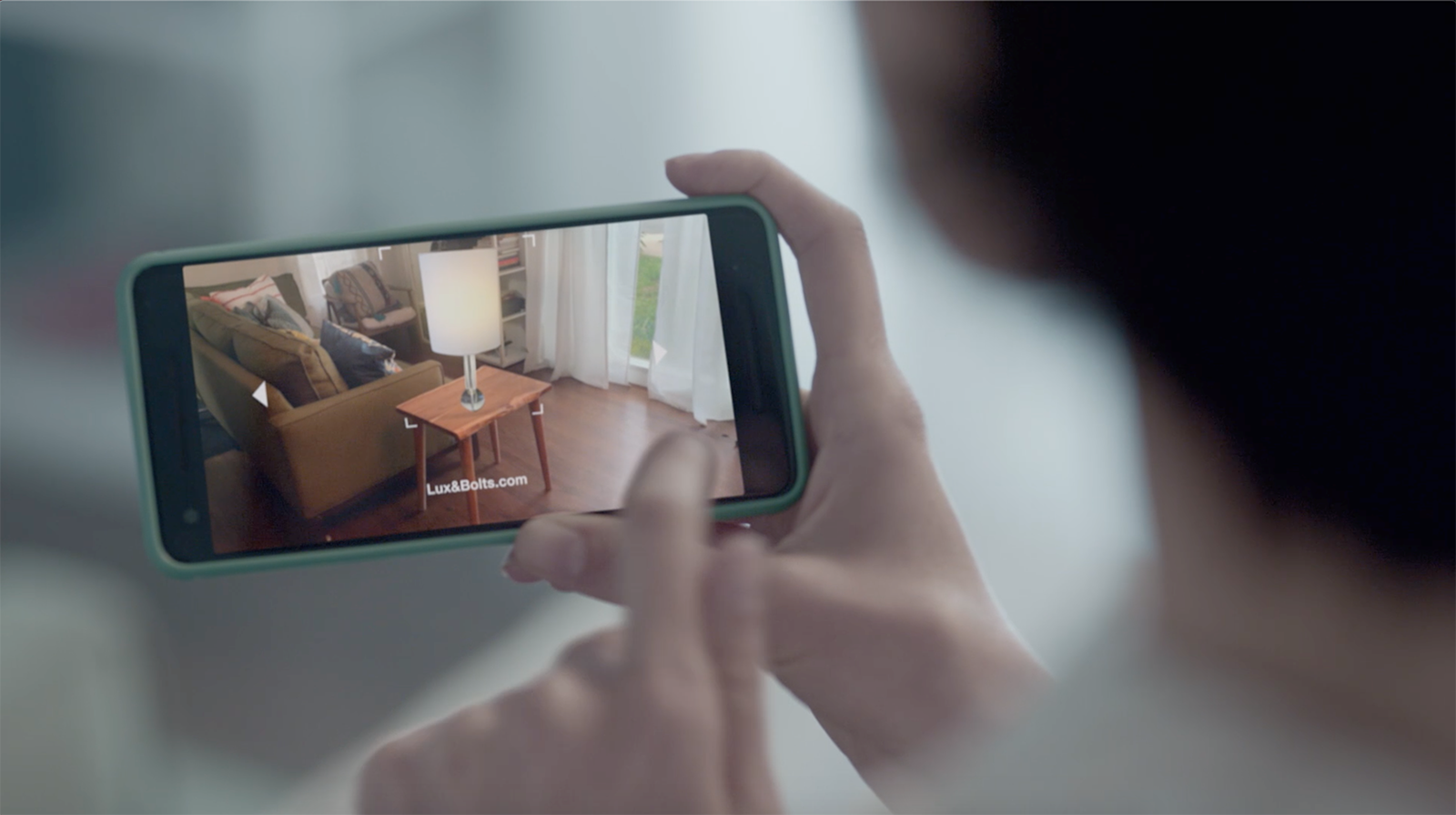 Person using augmented reality on their mobile phone to see how a product would look in their home.
