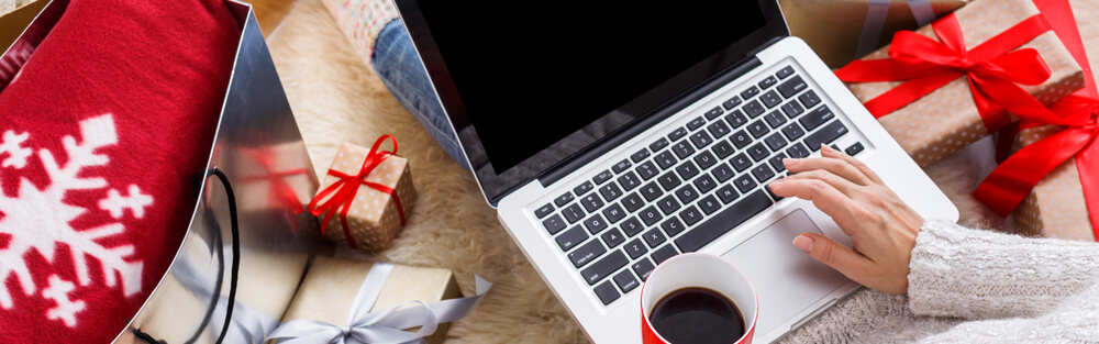 Someone on the floor with a cup of coffee, their computer, and holiday gifts.