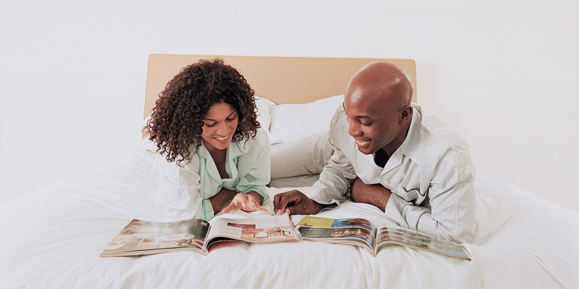 A couple reading magazines in bed.