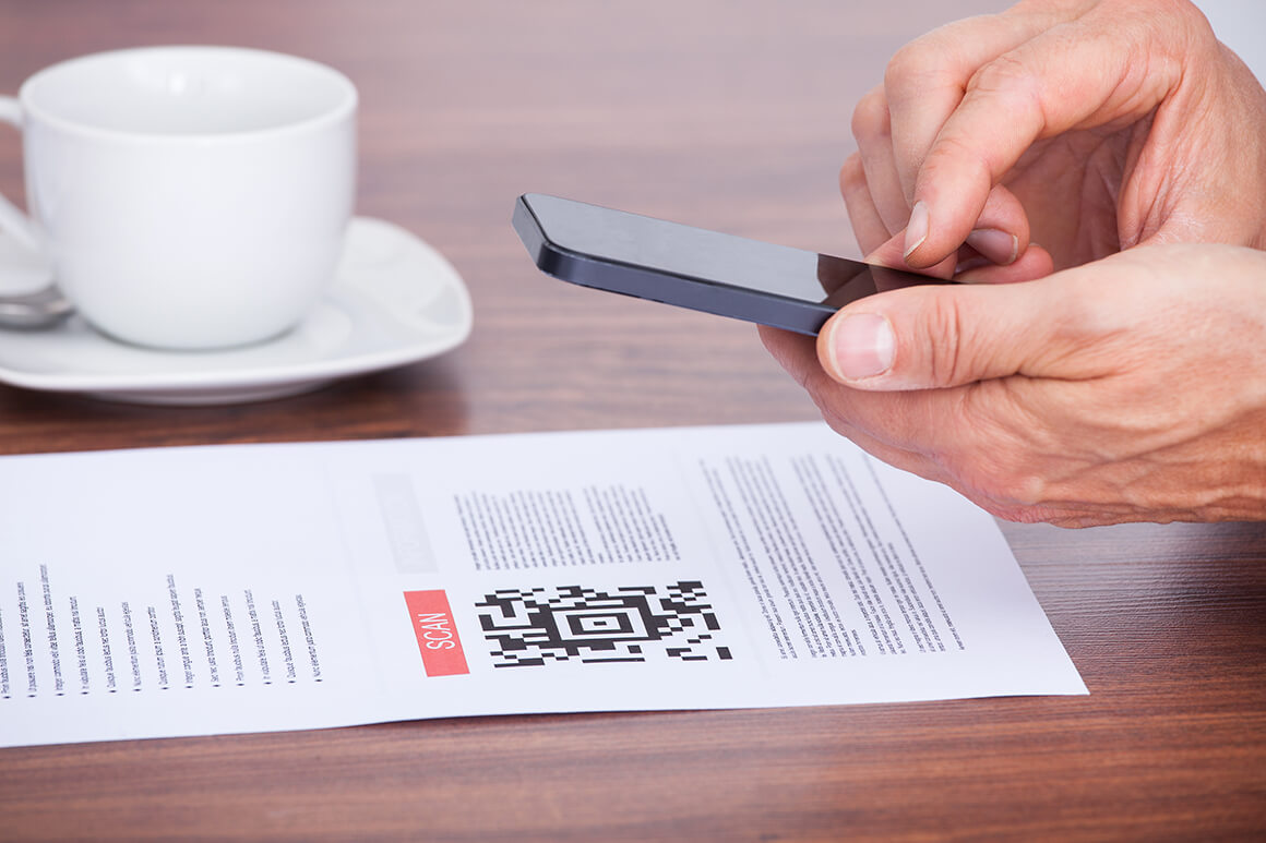 Person scanning a QR code with their phone at their desk.