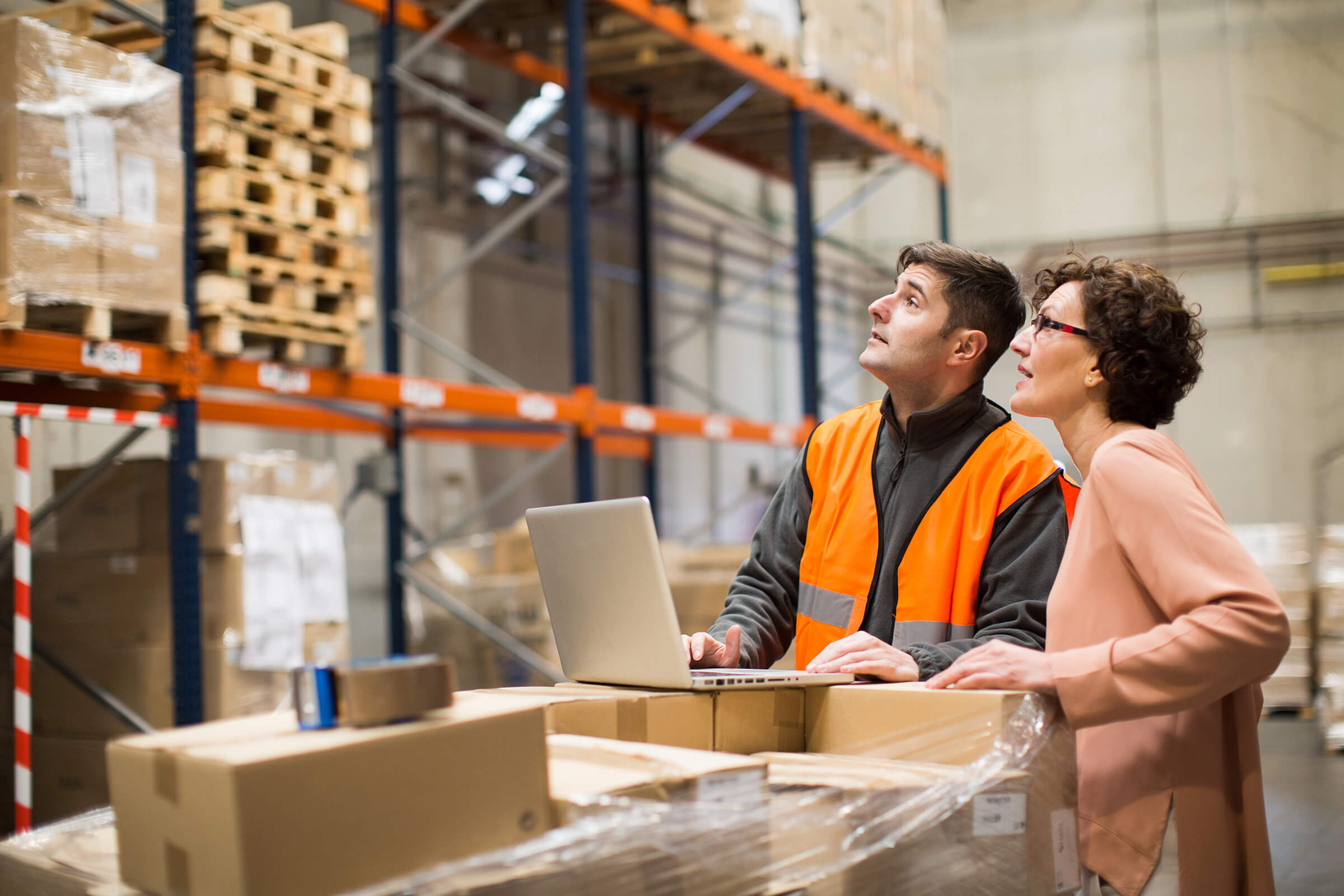 Two warehouse workers with a laptop assessing supplies on warehouse shelves.