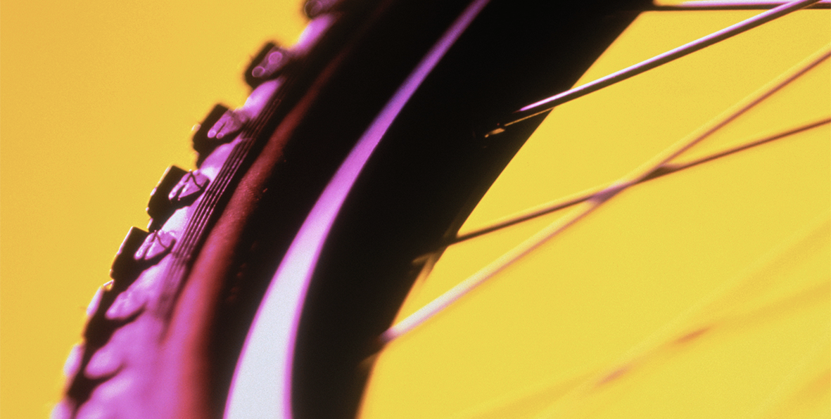Yellow tire tread on a bicycle wheel.