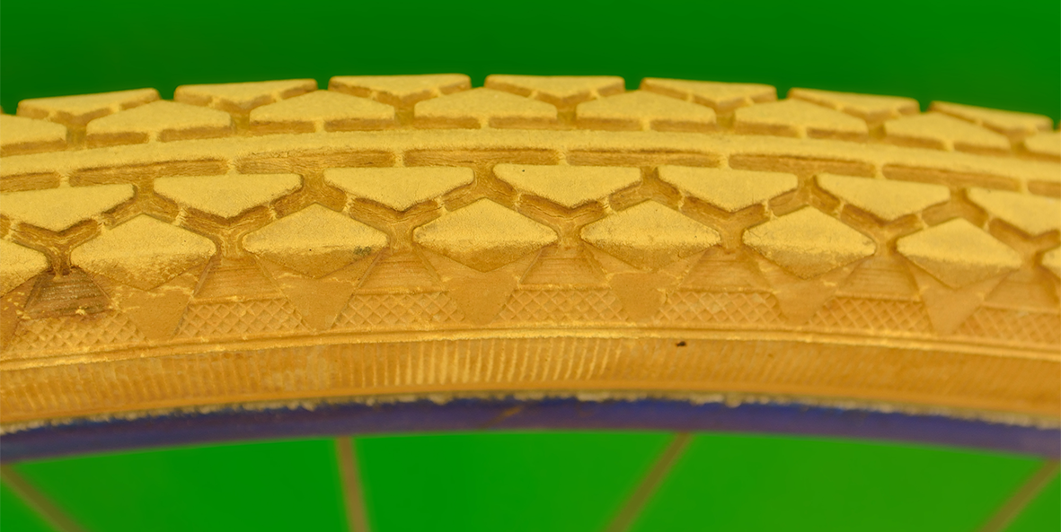 A close-up of a golden tire on green background.
