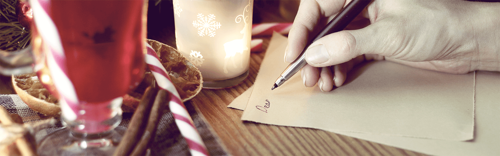 Someone writing a letter beside holiday decorations, including a candy cane and a candle.