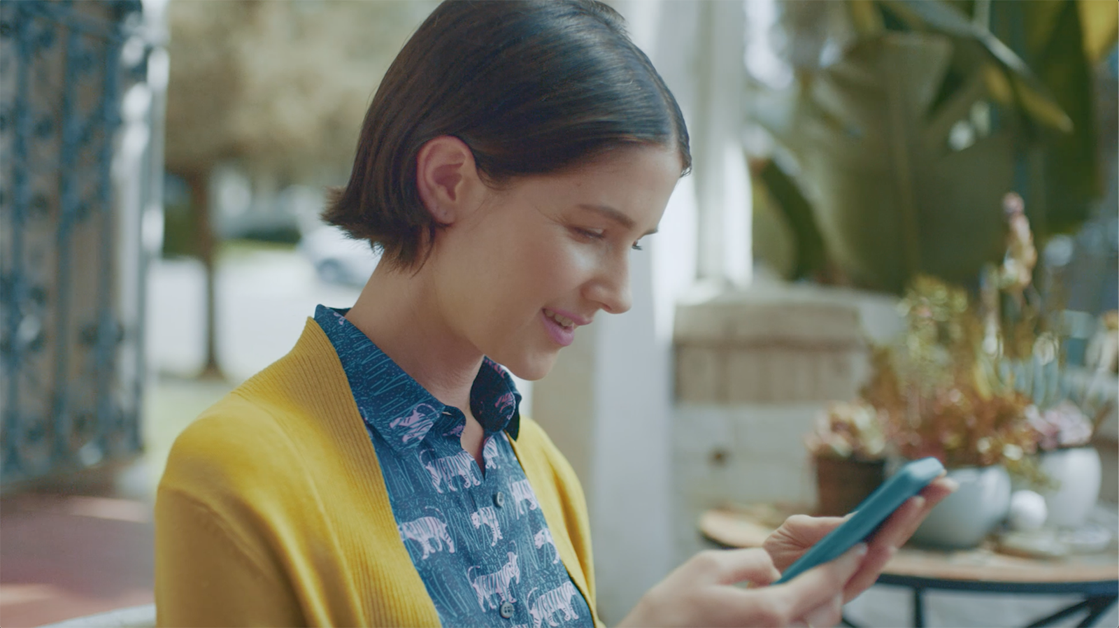 A woman looking at her mobile phone and smiling.
