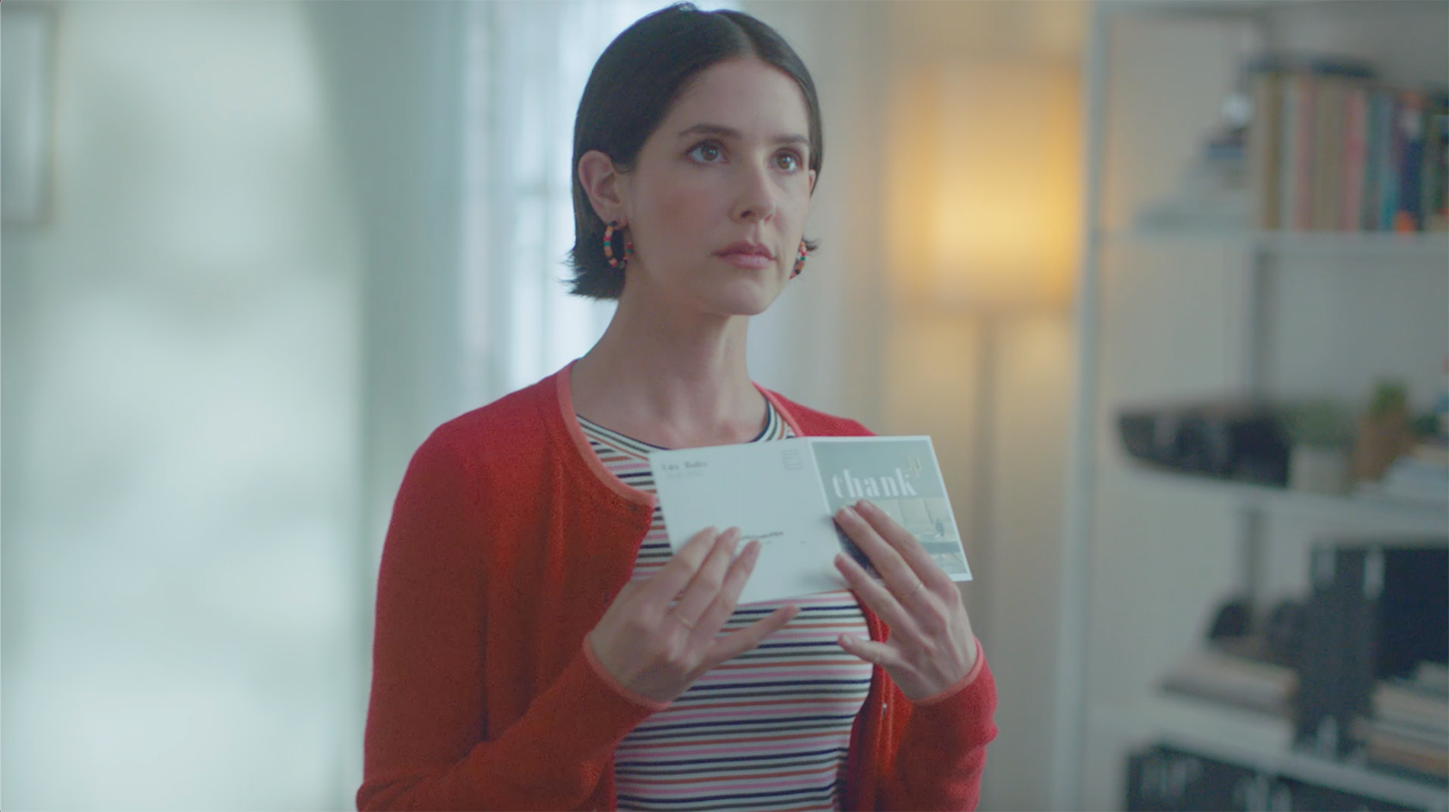 A woman reacting to a business's thank you card.