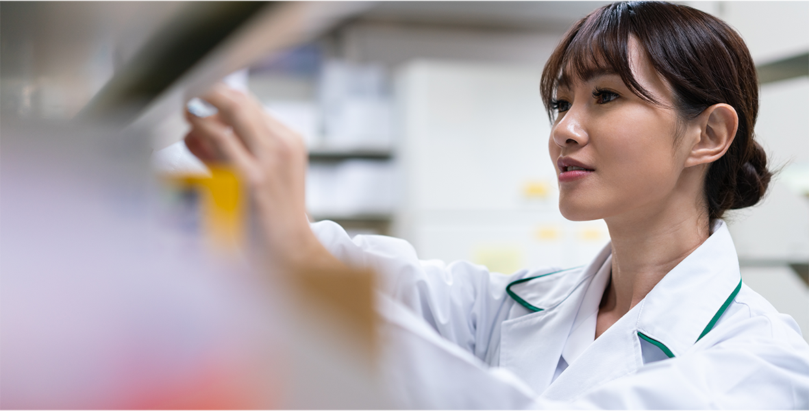 A woman in a white lab coat focused on her task.